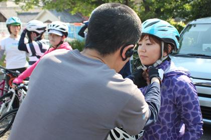 ヘルメットのつけ方を教わる参加者