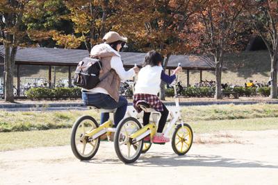タンデム自転車を楽しむ親子連れ
